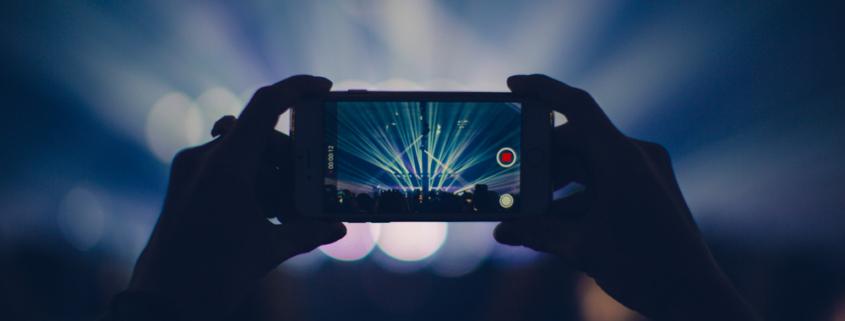 2 handen houden een smartphone vast die een concert aan het opnemen is met zijn smartphone