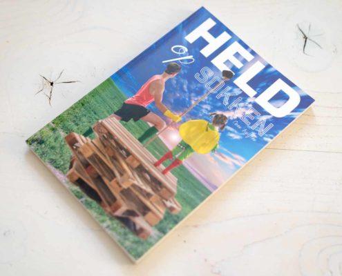 De cover van de eerste druk van Held op Sokken ontworpen door NOBLY Authentieke Communicatie & Creatie