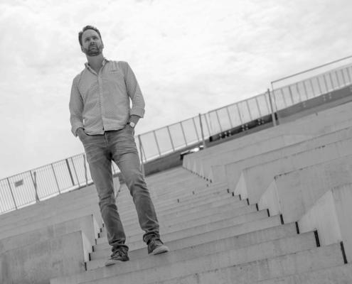 Foto van een Jeroen Meens bij Cynex die op een betonnen trap staat en een testimonial geeft voor een bedrijfsvideo van Yuki gemaakt door NOBLY Authentieke Communicatie & Creatie