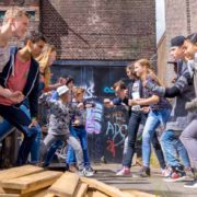 Jongeren staan in een steegje op een helder dag. Op de voorgrond liggen planken. Inde achtergrond is een deur te zien met graffiti. Het lijkt alsof de jongeren op het punt staan om te gaan vechten