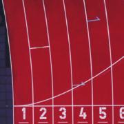 Een rode hardloopbaan, recht van boven gefotografeerd. De cijfers 1 tot en met 8 zijn zichtbaar