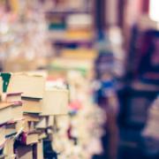 Een ruimte met een groot aantal boeken, de boeken liggen schots en scheef en veel boeken zijn vergeeld