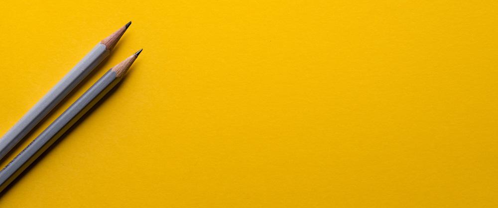 2 grijze potloden op een gele achtergrond