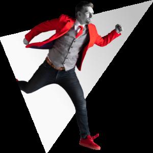 Renaldo springt uit een driehoeh in een rood NOBLY pak
