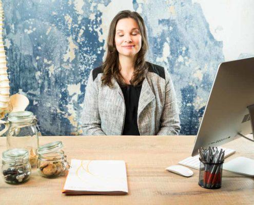Lisanne van Spotonmedics zit achter een bureau met haar ogen dicht op de set voor de bedrijfsvideo gemaakt door NOBLY