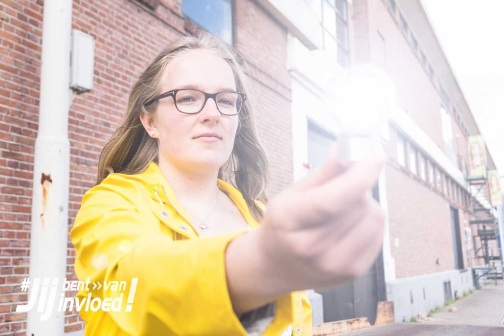 A teenage girl is holding a light bulb