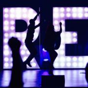 Een foto van het podium waar artiesten staan te springen met op de achtergrond de letters FREE
