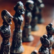 Oude schaakstukken van metaal. De stukken zelf zijn erg gedetailleerd vormgevingen, de stukken staan in hun beginpositie