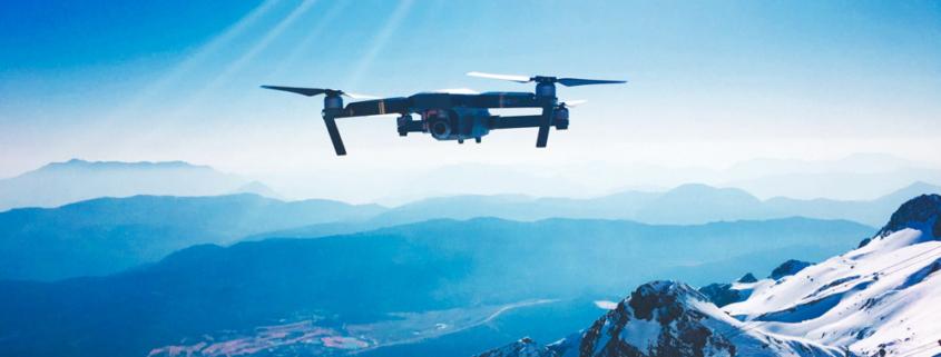 Een drone vliegt over een gebergte heen en maakt opnames